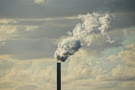 White smoke emerging from a smokestack, against a backdrop of clouds.