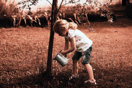 a young girl watering a tree
