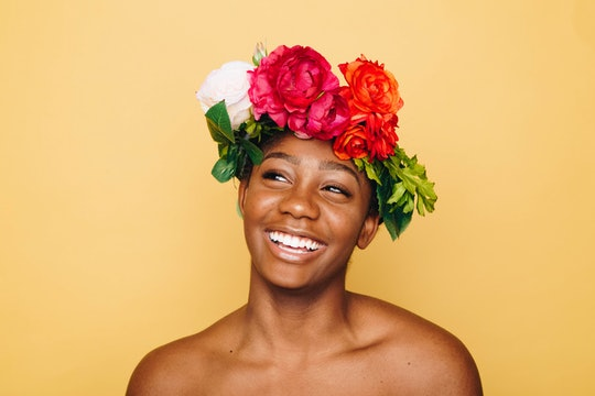 A smiling woman wearing a headdress made of flowers.