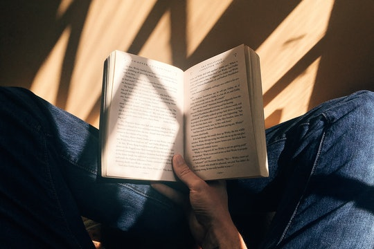 A person holding open a book seen from above