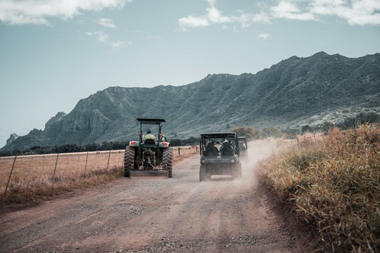 two tractors drive down a very dusty road