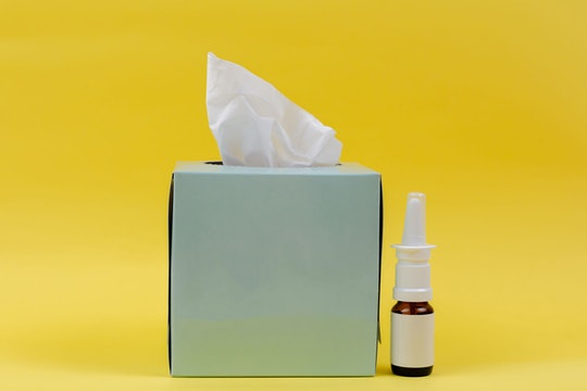 tissue box and allergy meds against a yellow background