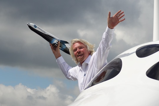richard branson hanging out of an airplane holding a small replica spaceship