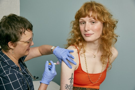 A woman with long red hair receiving a vaccination shot