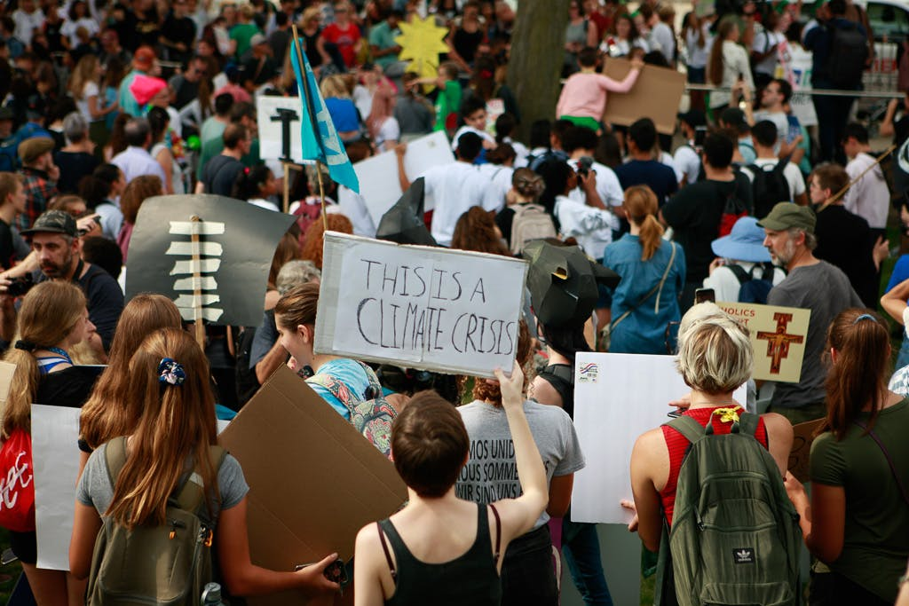"A shot of the backs of a crowd of climate strikers in Chicago, IL, USA. One is holding a sign that reads ""This is a climate crisis."""