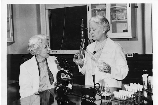Microbiologist Elizabeth Lee Hazen and chemist Rachel Brown, standing at a table with a microscope and culture tubes.