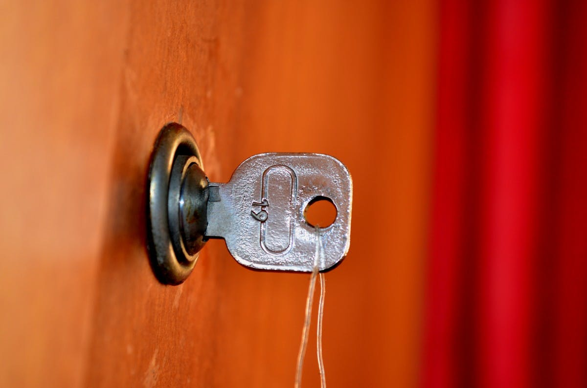a key in a lock against an orange-brown background