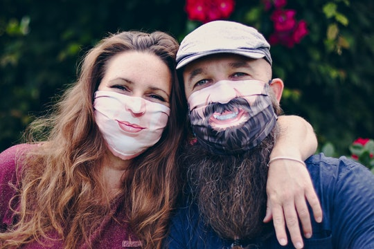A man and woman wearing face masks with smiles printed on them
