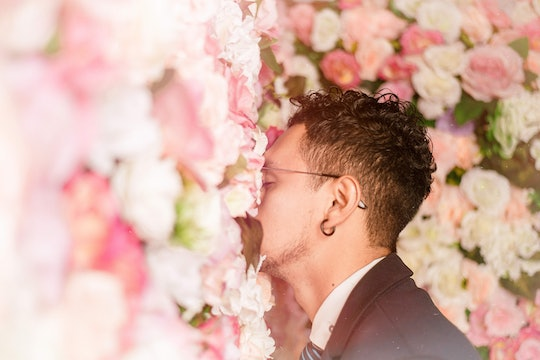 a person with his face pressed into a wall of flowers