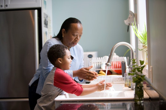 A woman and child washing their hands at the sink