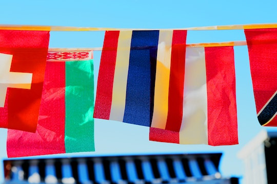 six different countries' flags hanging against a blue sky