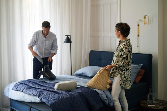 a couple making their bed and getting ready for the day in a white room with blue furniture