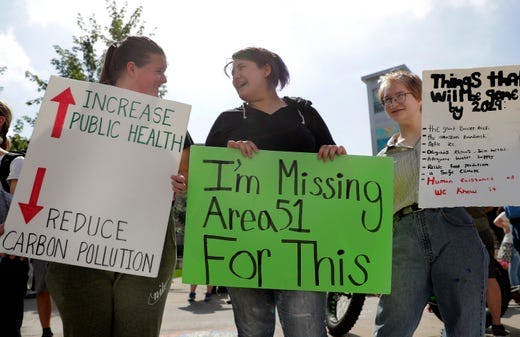 "Climate strikers in Appleton, WI, USA, holding signs, one of which reads ""I'm missing Area 51 for this."""