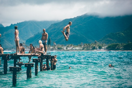 people jumping and swimming in a lake