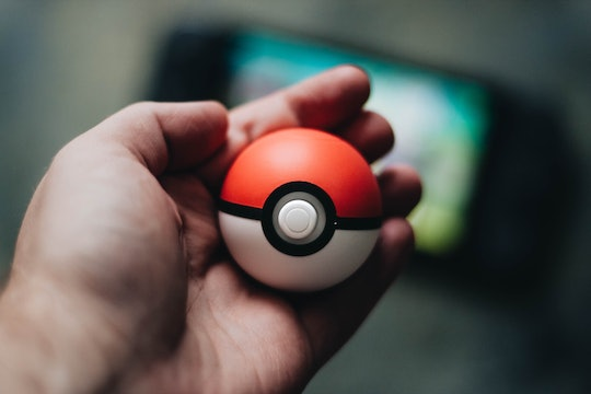 A person holding a model of a red and white pokeball from Pokemon