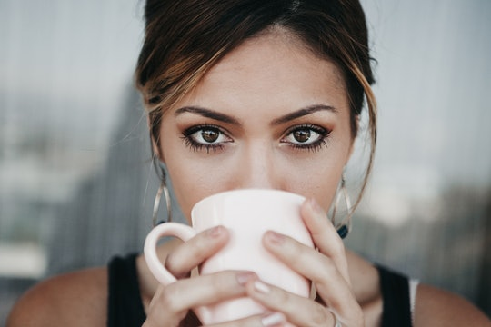 a woman drinking coffee and looking at the camera