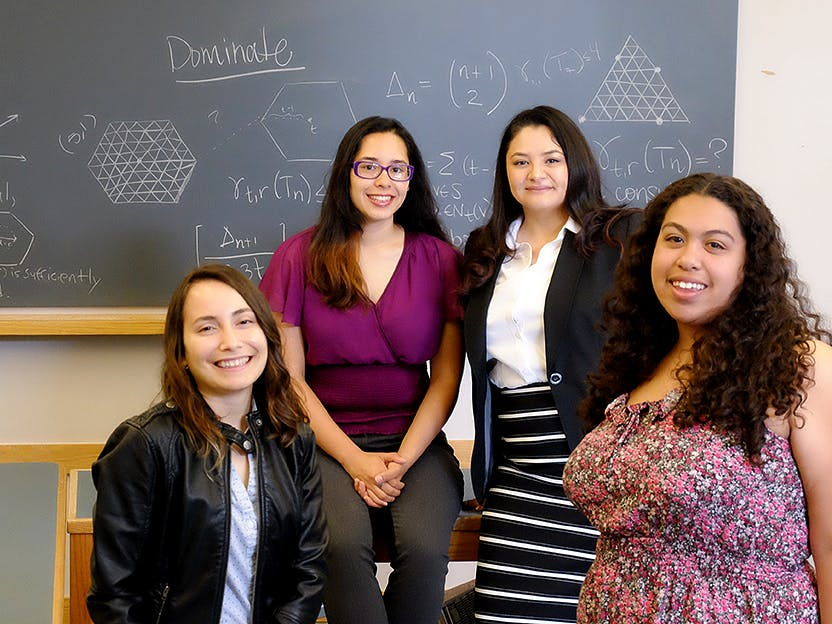 pamela harris and three students smile in front of a math-filled chalkboard
