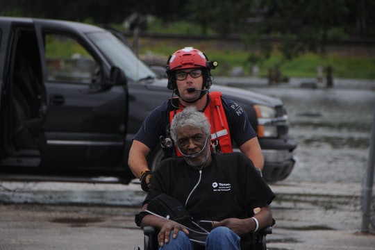 a soldier wheeling another man to a vehicle for hospital transport in a flooded parking lot