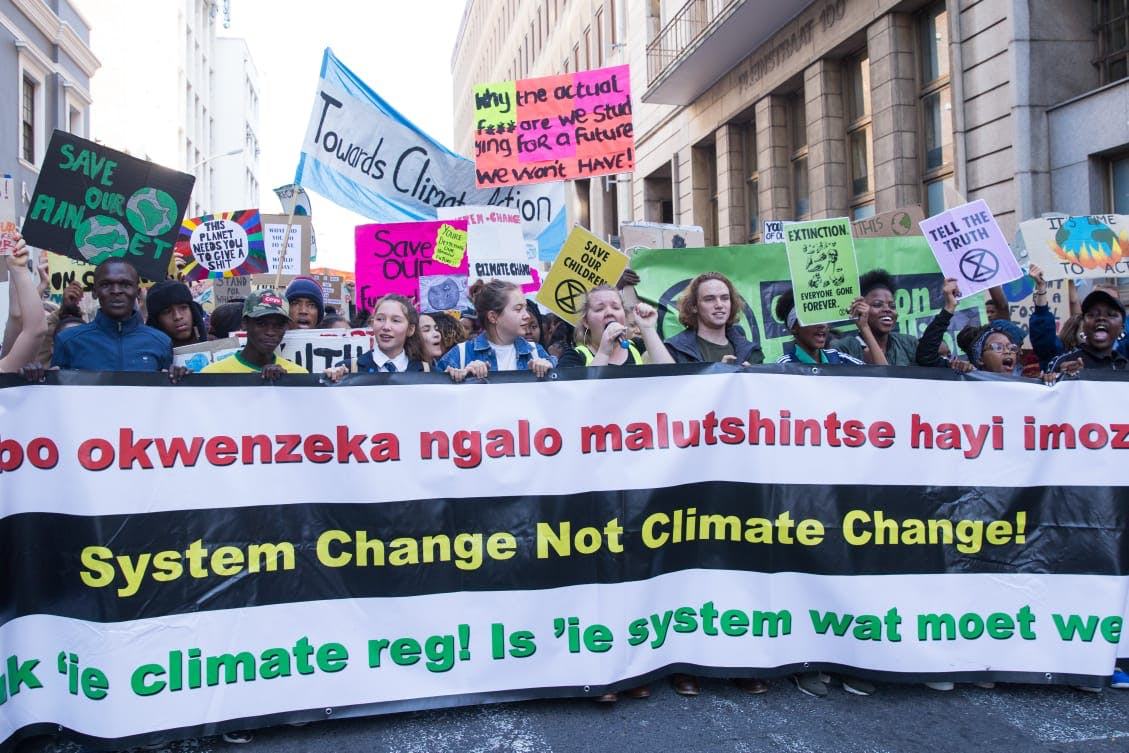 "Climate strikes in South Africa holding a large sign that reads ""System Change Not Climate Change!"""