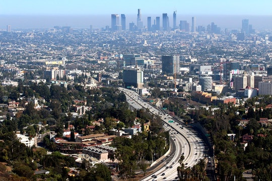 a shot of a freeway into a big city, with hazy air pollution in the distance