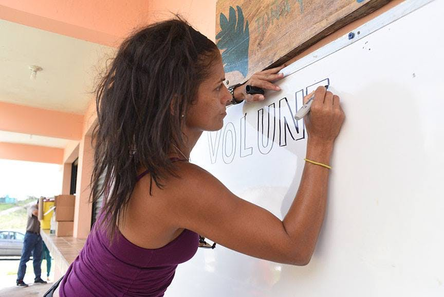 "A woman in Puerto Rico writes the word ""VOLUNTEER"" on a whiteboard after Hurricane Maria."