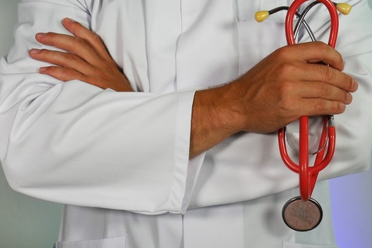 the upper body of a doctor holding a stethoscope