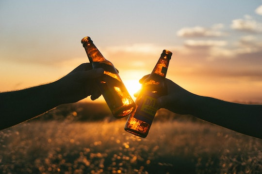 Two people cheersing their beers against a sunset.