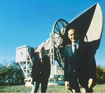 two men in suits in front of a large piece of machinery
