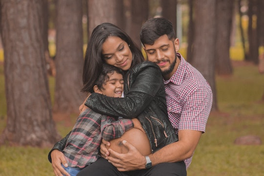 a pregnant woman hugging a man and child