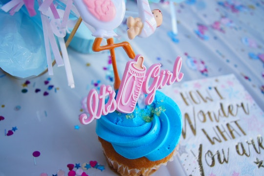 "Gender reveal cupcake with blue icing and a pink ""it's a girl"" decoration"