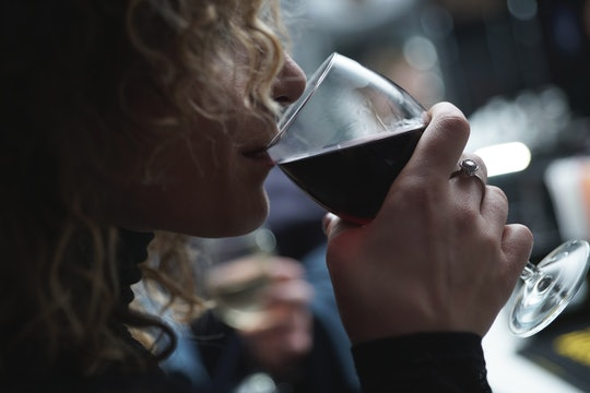 side view of woman drinking a glass of wine