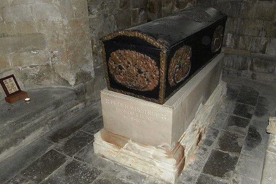 a coffin on a pedestal in a stone room