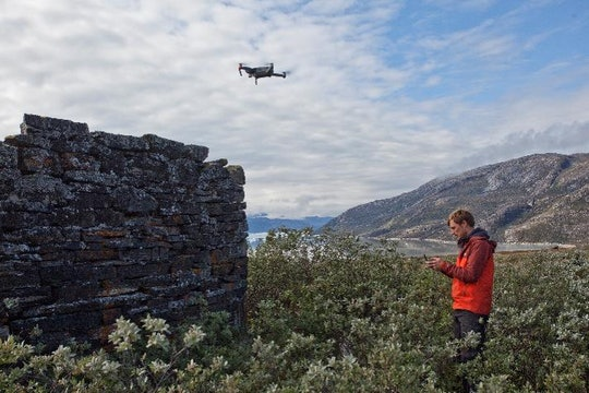A scientist pilots a drone over the ruins of a stone structure in a grassy field.