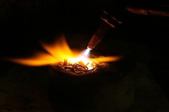 a welder using a torch to melt metal
