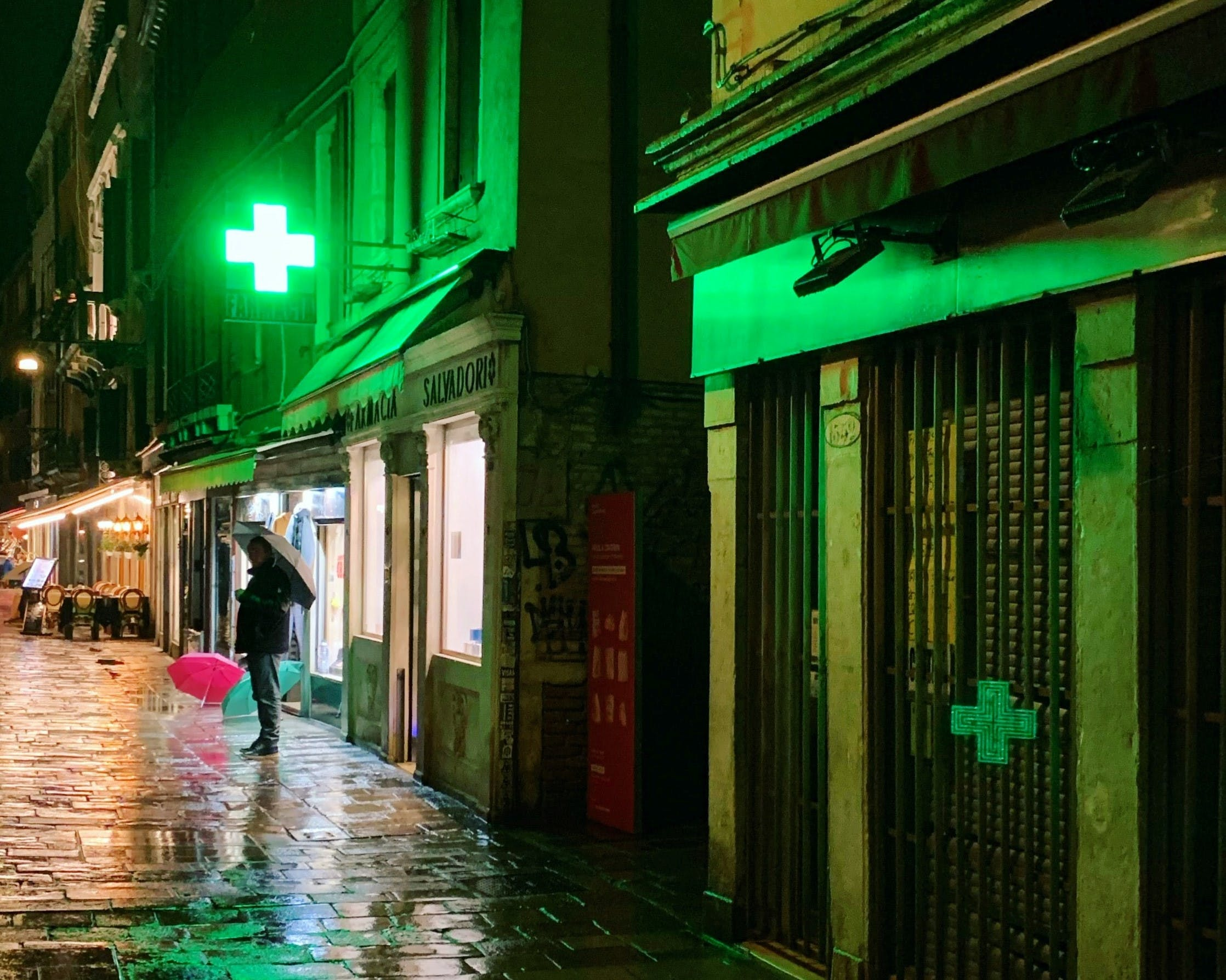 A pharmacy with a neon green cross sign on a rainy street at night