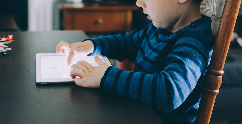 a young boy playing on a tablet computer