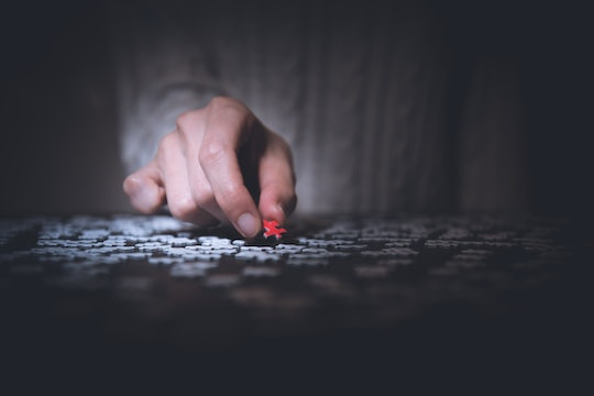 a hand picking up a red puzzle piece