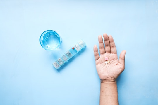 a hand holding some pills next to a pill keeper and a glass of water