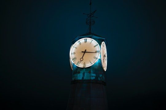 lit up clock tower in darkness