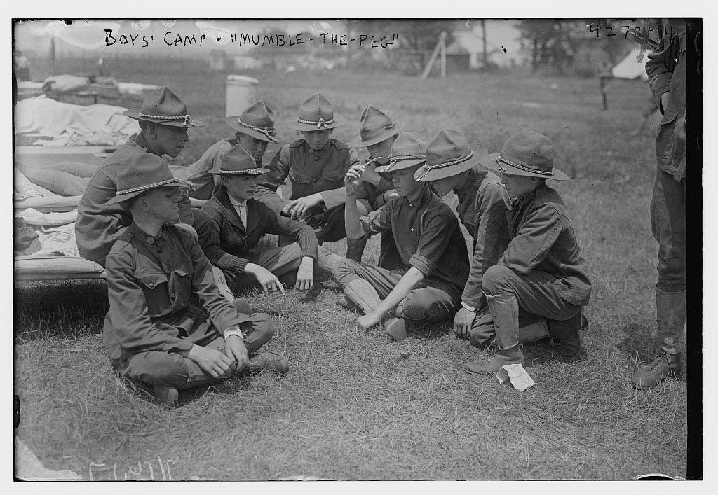 "Boys sitting cross-legged on the ground playing ""mumble-the-peg"" knife game"