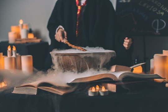 person in robes stirring a smoking cauldron