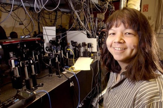 A photo of Deborah Jin with some lab equipment