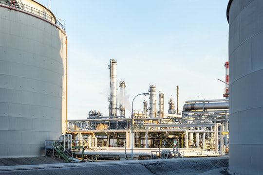 a shot of buildings and pipes in an oil refinery