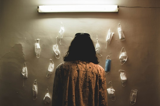 a woman staring at masks hanging on a wall. almost all masks are white, but one is blue