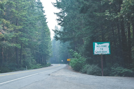"""a photo of a tree-lined road and a sign that says """"welcome to oregon"""""""