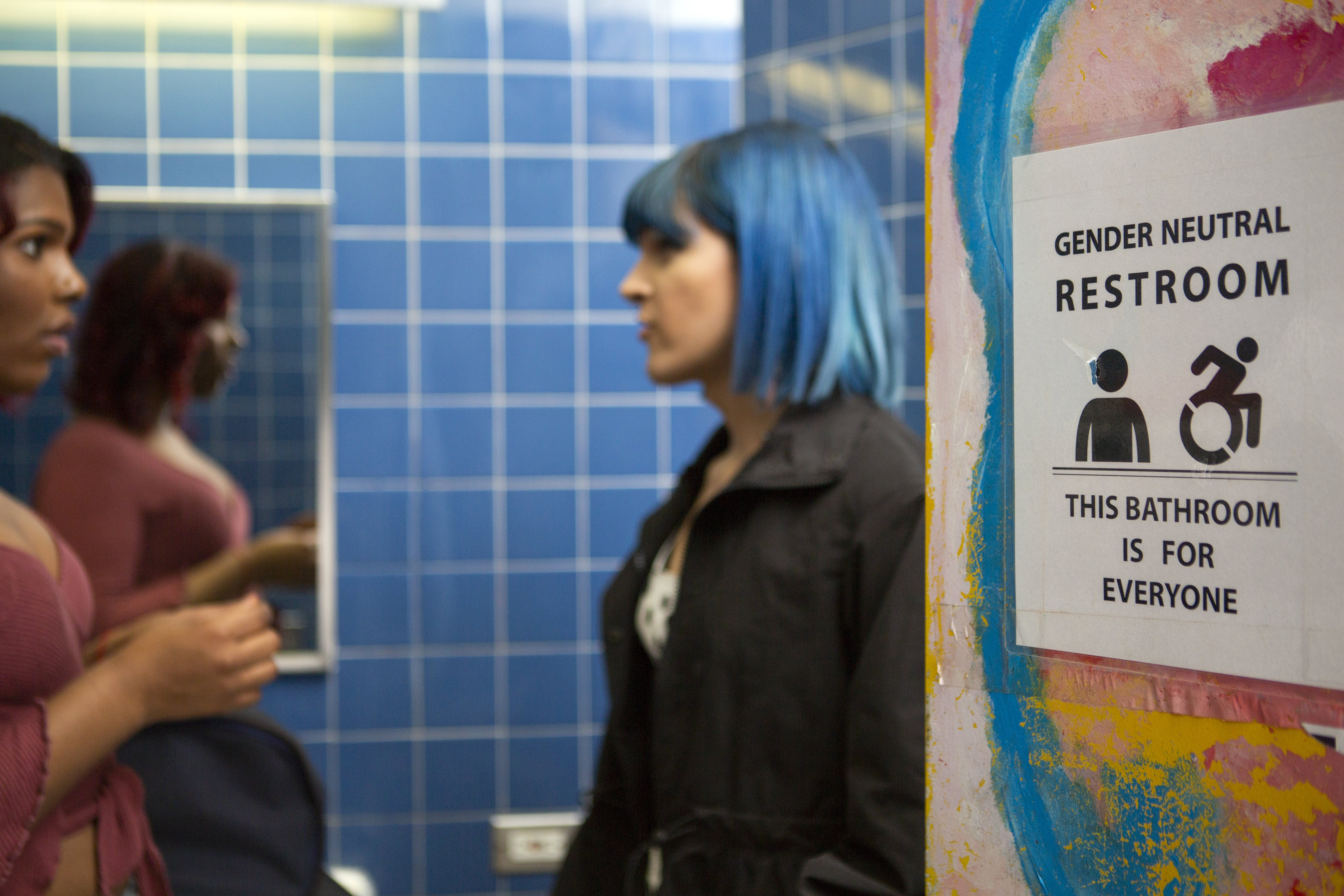 Two students talk in a gender neutral bathroom.