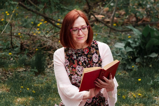 a woman reading from a book outside