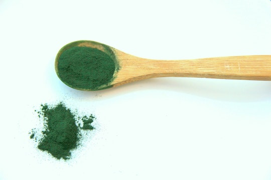 a green powder scooped up in a wooden spoon