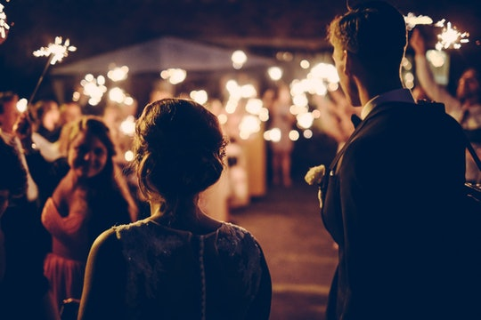 a wedding photo taken from behind the bride and groom looking at the crowd