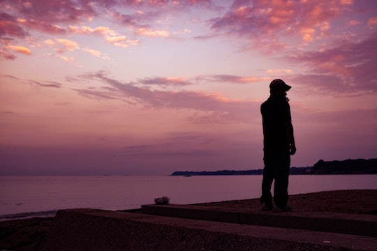 a man standing outside in the sunset